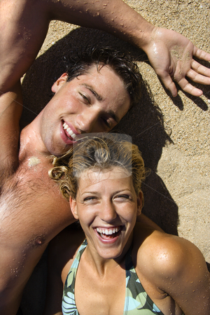 Laughing couple. stock photo, Smiling happy couple lying in sand on Maui, Hawaii beach. by Iofoto Images