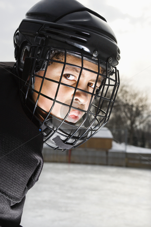 Ice hockey player boy. stock photo, Ice hockey player boy in uniform and cage helmet making mean face. by Iofoto Images