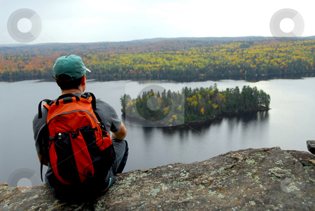 Hiker stock photo, A hiker sitting on a cliff edge enjoying scenic view by Elena Elisseeva