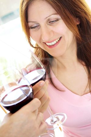 Mature woman toasting with red wine stock photo, Smiling mature woman toasting with a glass of red wine by Elena Elisseeva