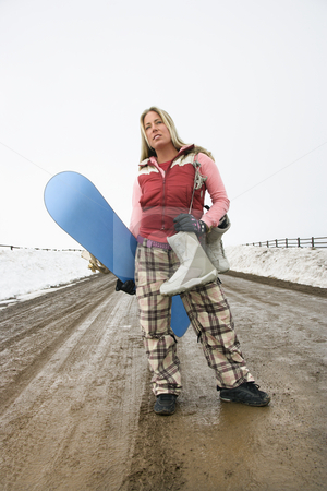 Woman holding snowboard. stock photo, Young woman in winter clothes standing alone on muddy dirt road holding snowboard and boots. by Iofoto Images