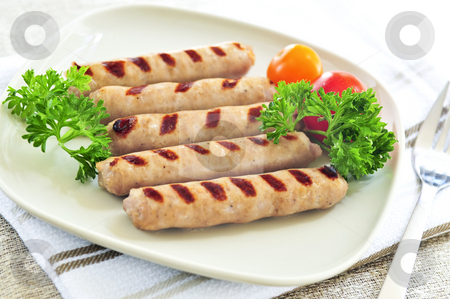 Breakfast sausages stock photo, Serving of grilled breakfast sausages on a plate by Elena Elisseeva
