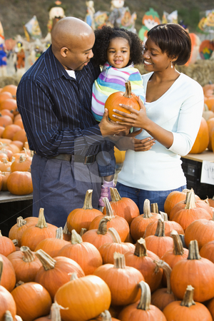 Family buying pumpkin. stock photo, Parents and daughter picking out pumpkin and smiling at outdoor market. by Iofoto Images