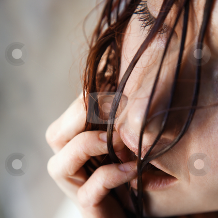 Woman face. stock photo, Close up of pretty young redhead woman with wet hair hanging in face putting fingers in mouth. by Iofoto Images