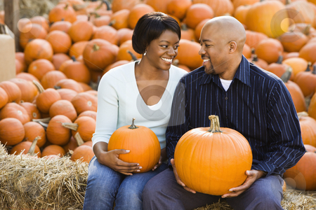 Couple Fall portrait. stock photo, Happy smiling couple sitting on hay bales and holding pumpkins at outdoor market. by Iofoto Images