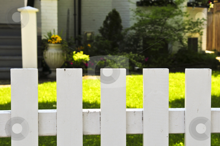 Front yard with white fence stock photo, White fence around front yard of residential house by Elena Elisseeva