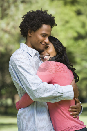 Couple embracing. stock photo, Attractive couple smiling and embracing in park. by Iofoto Images