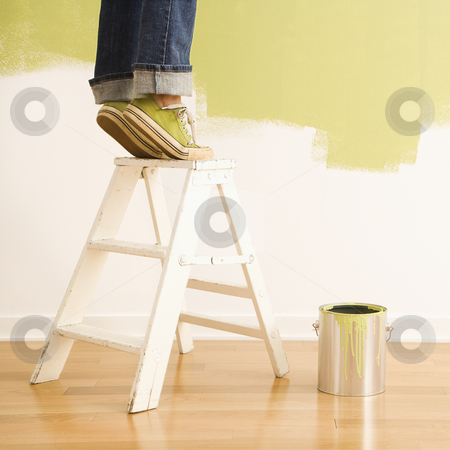 Woman on ladder painting. stock photo, Legs of woman standing on tiptoe on stepladder with paint can and painted wall. by Iofoto Images