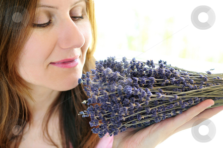 Woman smelling lavender stock photo, Mature woman smelling bunch of dried lavender by Elena Elisseeva