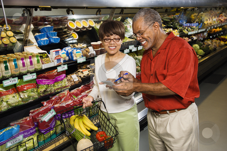 Couple in grocery store. stock photo, Middle aged African American man and woman in grocery store smiling and pointing at shopping list. by Iofoto Images