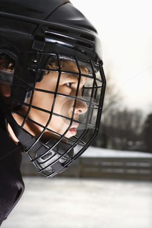 Ice hockey player boy. stock photo, Ice hockey player boy in uniform and cage helmet concentrating. by Iofoto Images