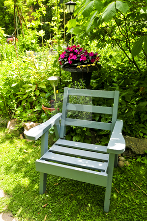Chair in green garden stock photo, Wooden chair in a secluded corner of lush green garden by Elena Elisseeva