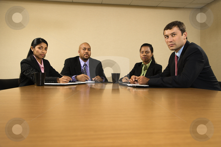 Serious business meeting. stock photo, Businesspeople sitting at conference table. by Iofoto Images
