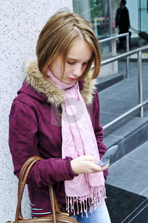 Teenage girl text messaging on cell phone stock photo, Teenage girl text messaging on cell phone by Elena Elisseeva