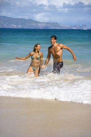 Couple on vacation. stock photo, Attractive couple embracing and smiling as they walk out of water in Maui, Hawaii. by Iofoto Images