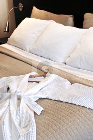 Hotel bed with bathrobe stock photo, Comfortable bed with clean bathrobe in upscale hotel by Elena Elisseeva