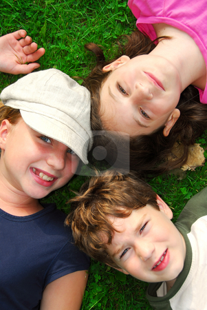 Children stock photo, Portrait of three young children lying on grass looking up by Elena Elisseeva