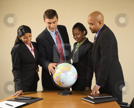 Businesspeople with globe. stock photo, Corporate businesspeople standing around world globe smiling and talking. by Iofoto Images