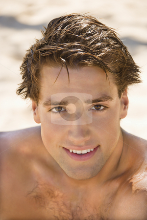 Smiling man. stock photo, Head and shoulder portrait of handsome man on beach. by Iofoto Images