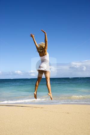Jumping woman. stock photo, Pretty young woman jumping on Maui, Hawaii beach with arms raised into air. by Iofoto Images