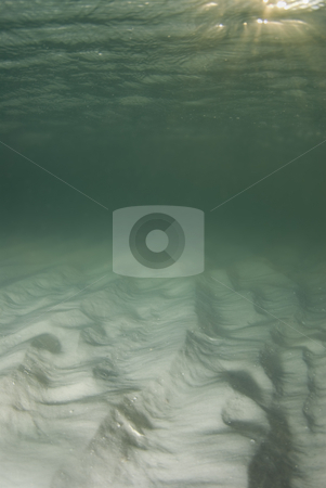 Sandy Bottom stock photo, A view of the rippled ocean floor, the action on the surface, and the sky and golden sunset rays breaking through the water in the top right corner. by A Cotton Photo