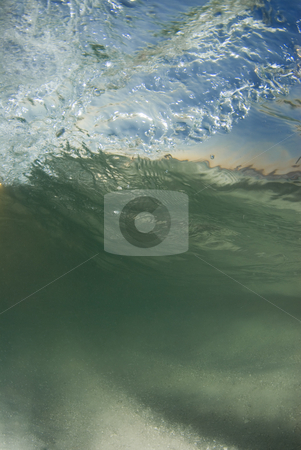 Curled Underwater stock photo, Underwater view of a curling, breaking wave; With the bright blue sky and sunset on the horizon coming through the surface and the stirring sand on the ocean floor by Amanda Cotton