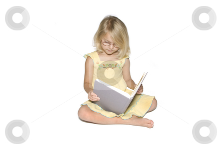 Little Girl Studying Right stock photo, A young blonde girl sitting crosslegged while reading a textbook.  Isolated on a white background by A Cotton Photo