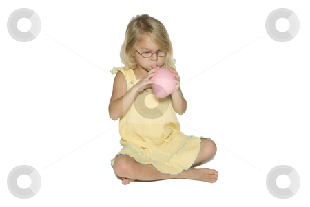 Girl Blowing up Balloon stock photo, A young girl in a yellow dress sitting down and blowing up a pink balloon.  Isolated on a white background by A Cotton Photo