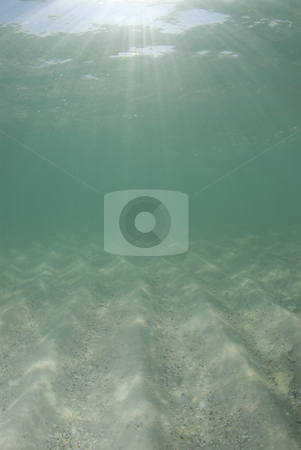 Underwater Beach Sunrays Sky View stock photo, Underwater view of sunbeams stream through the surface of the ocean and dancing on the floor of the sea on a bright sunny day.  Bright sand and blue sky. by Amanda Cotton