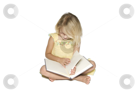 Little Girl Reading stock photo, A young blonde girl sitting crosslegged while reading a textbook.  Isolated on a white background by A Cotton Photo