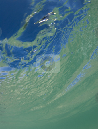Watercolors stock photo, Underwater view of the surface of the ocean, with the ripples casting an abstract shift between the water, the reflection of the sand, and the bright blue clear sky above. by A Cotton Photo