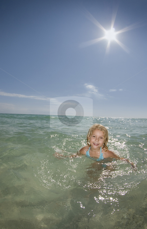 Girl Playing in Ocean stock photo, A young girl plays in the ocean on a calm bright sunny day by A Cotton Photo