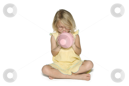 Girl Smiling and Inflating Balloon stock photo, A young girl in a yellow dress sitting down and blowing up a pink balloon.  Isolated on a white background by A Cotton Photo