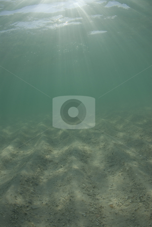 Underwater Beach Sunrays Sky and Sand stock photo, Underwater view of sunbeams stream through the surface of the ocean and dancing on the floor of the sea on a bright sunny day. by A Cotton Photo