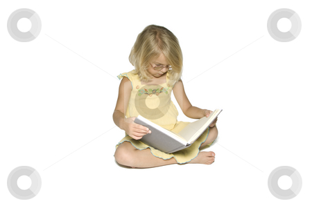 Little Girl Studying Left stock photo, A young blonde girl sitting crosslegged while reading a textbook.  Isolated on a white background by A Cotton Photo