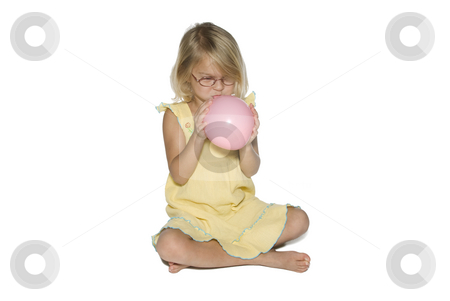 Girl Inflating Balloon stock photo, A young girl in a yellow dress sitting down and blowing up a pink balloon.  Isolated on a white background by A Cotton Photo