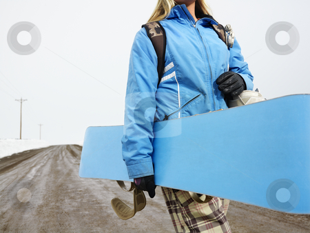 Woman carrying snowboard. stock photo, Young woman in winter clothes walking alone down muddy dirt road holding snowboard and boots. by Iofoto Images