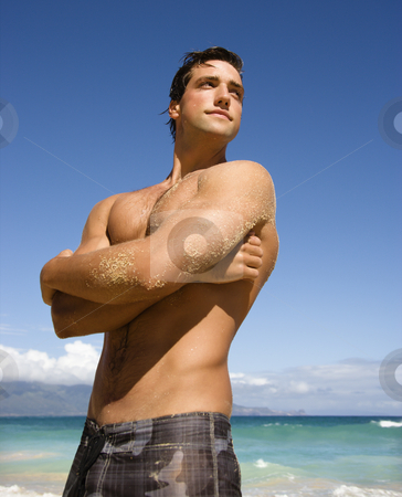 Handsome man. stock photo, Handsome man standing on Maui, Hawaii beach. by Iofoto Images