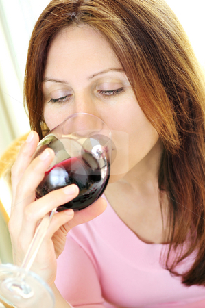 Mature woman with a glass of red wine stock photo, Mature woman drinking from a glass of red wine by Elena Elisseeva