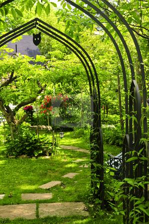 Lush green garden stock photo, Lush green garden with wrought iron arbor by Elena Elisseeva