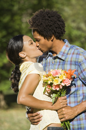 Couple kissing. stock photo, Woman and man embracing and kissing in park. by Iofoto Images