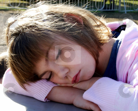 Child taking a Nap stock photo, A small child rests her head on her arms while waiting for the fun to begin at the fair by Marburg