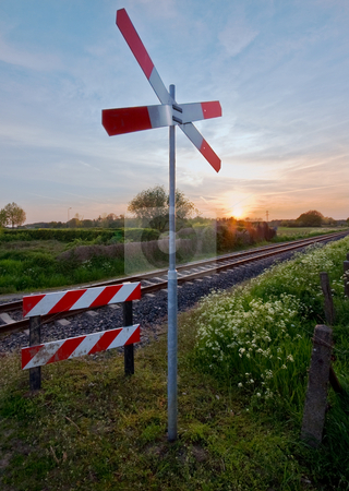 Railway tracks with pastel sunset stock photo, Railway tracks with pastel sunset and traffic sign by Karin Claus