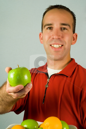 Offering stock photo, A young man offering a fresh apples by Richard Nelson