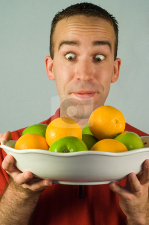 Diet stock photo, A man looking at a bowl of apples and oranges wide eyed by Richard Nelson