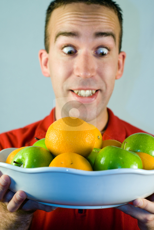 Apples and Oranges stock photo, A man looking at a bowl of apples and oranges by Richard Nelson