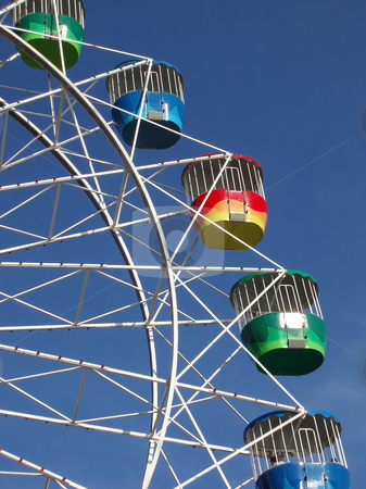 Ferris wheel stock photo, A colourful fairground wheel against a blue sky by Stephen Gibson