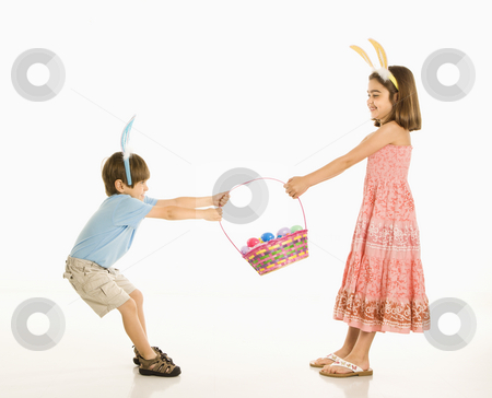 Children with Easter basket. stock photo, Boy and girl wearing bunny ears fighting over Easter basket. by Iofoto Images