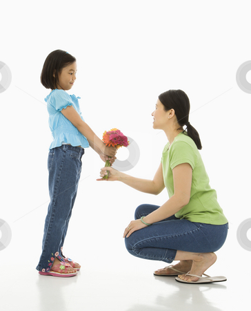 Girl giving mother flowers. stock photo, Asian girl handing bouquet of flowers to her mother. by Iofoto Images
