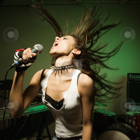 Female singing into mic. stock photo, Caucasian female swinging head and hear while singing into microphone. by Iofoto Images